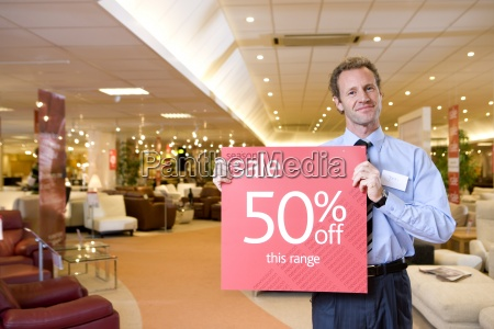salesman with sale sign in furniture