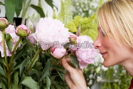 woman smelling flowers in flower shop