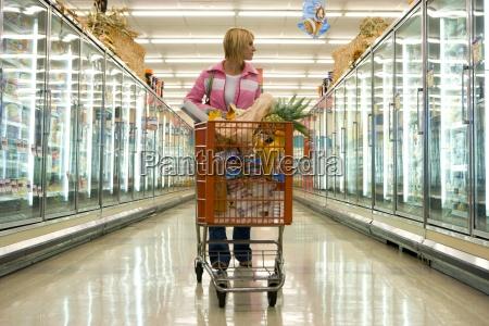 frau lebensmittelgeschaeft beim einkaufen in tiefkuehlkost
