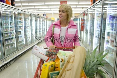 frau einkaufen in tiefkuehlkost abschnitt