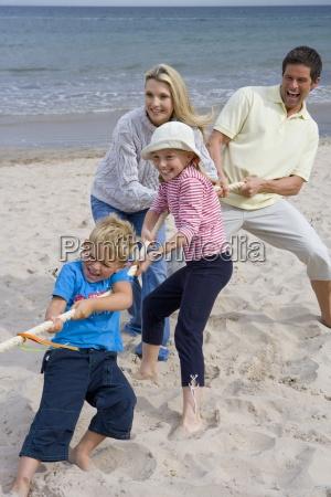 junge familie spielen tauziehen am strand