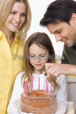 junges maedchen mit familie haelt geburtstagstorte