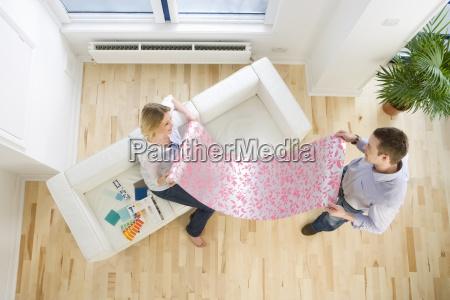 paar sucht auf tapetenprobe im wohnzimmer