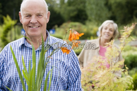 senior couple standing in garden centre