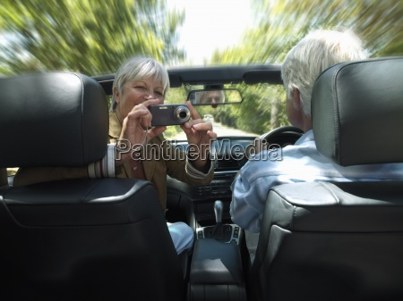 senior couple driving in convertible car