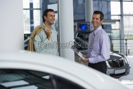 car salesman standing with male customer