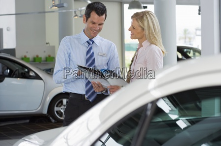 car salesman standing with female customer