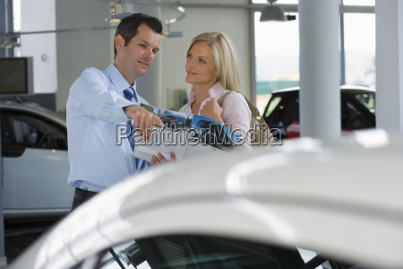 car salesman pointing out new car