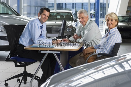 car salesman and senior couple sitting
