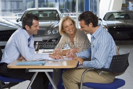 car salesman and couple sitting at