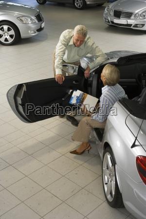 senior couple looking at silver convertible