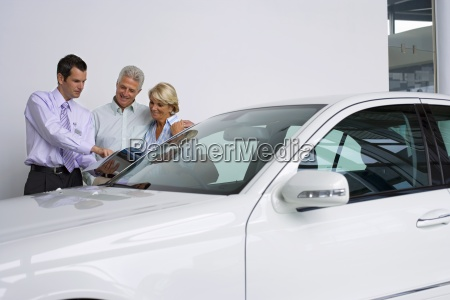 car salesman showing senior couple new