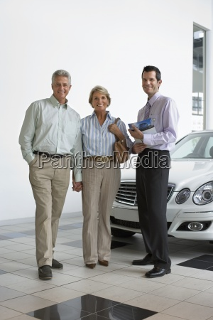 car salesman and senior couple standing