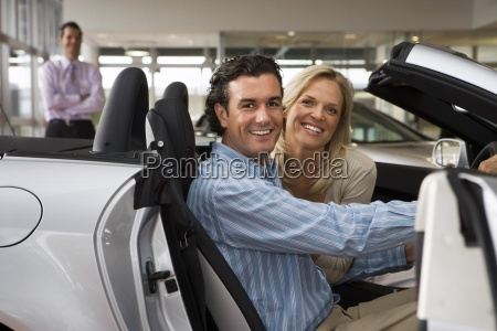 car salesman standing in large car