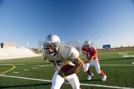 american football spieler jagen gegnerischen spieler