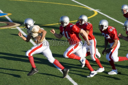 american football players chasing opposing player