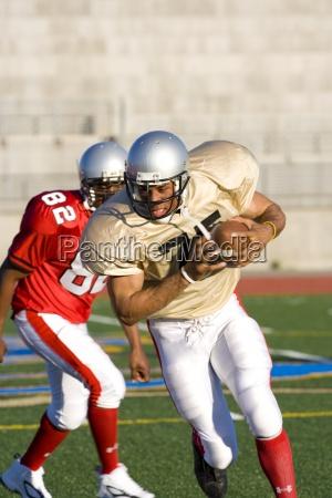 american football player chasing opposing player