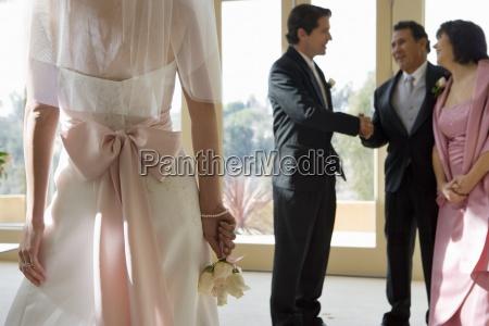 groom talking to senior couple at
