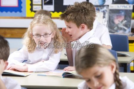 school boy whispering to girl in