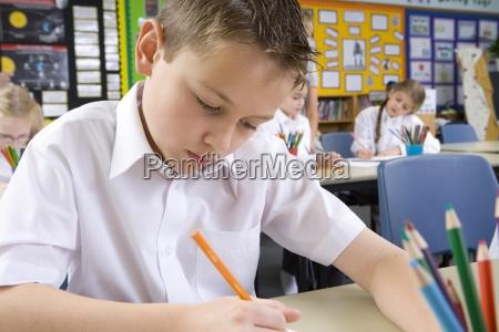 schuljunge schreiben im klassenzimmer