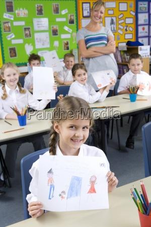 stolze schulkinder zeichnungen im klassenzimmer vorfuehrt