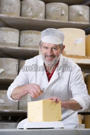 portrait of smiling cheese maker cutting