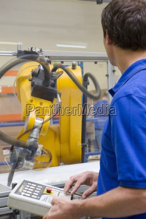 arbeiter beobachten roboterarm arbeitet an fliessband