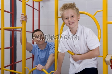 sportlehrer helfen student aufstieg turnhalle kletterausruestung