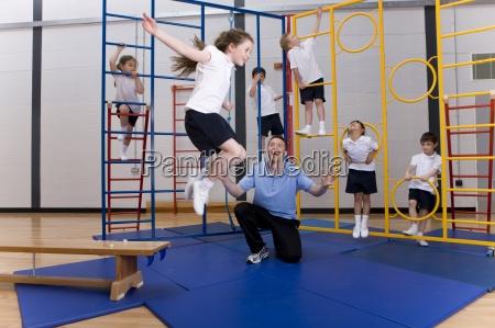 gym teacher watching school girl jumping