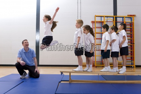 gym teacher watching school girl jump