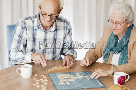 a senior couple playing a board