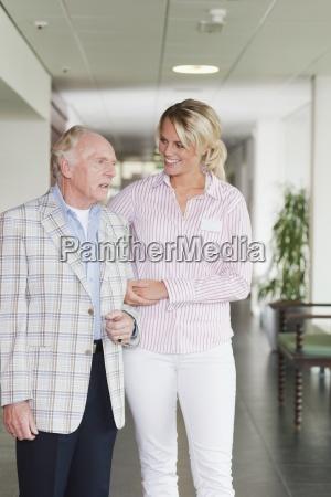 ein aelterer mann zu einer pflegehelferin