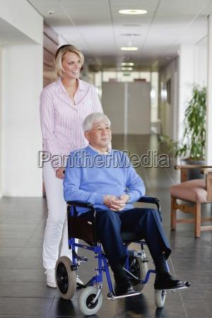 eine pflegekraft treibt ein aelterer mann