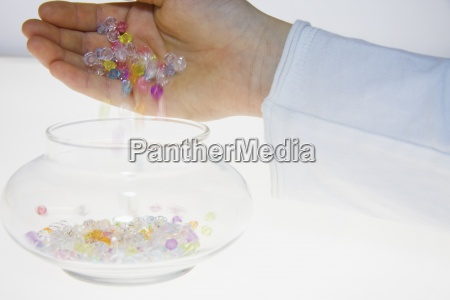 eine person eingiessen farbigen perlen in