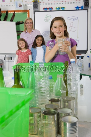 teacher and students sorting recyclables in