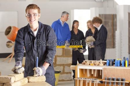 student mit hammer und meissel in