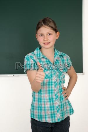schuelerin in schule haelt daumen hoch