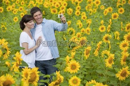 smiling couple taking self portrait among