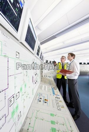 ingenieure suchen auf monitoren im kontrollraum