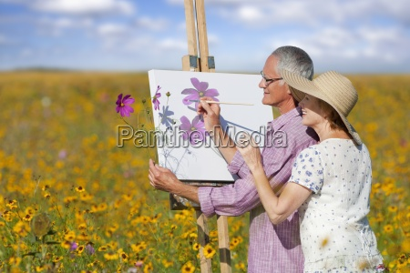 smiling senior couple painting in sunny