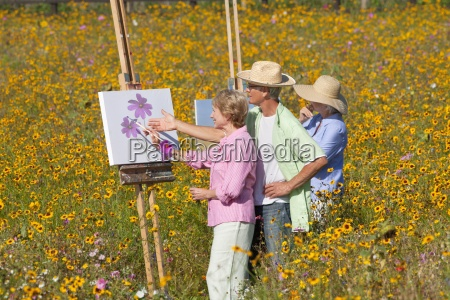 smiling seniors painting in sunny wildflower