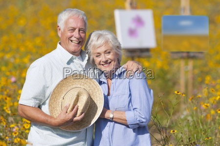 portrait of smiling senior couple painting