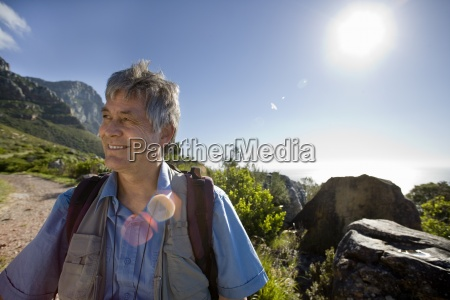 aeltere menschen mit rucksack auf bergweg