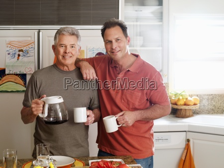 senior man and adult son holding