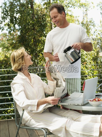 couple relaxing on balcony man pouring