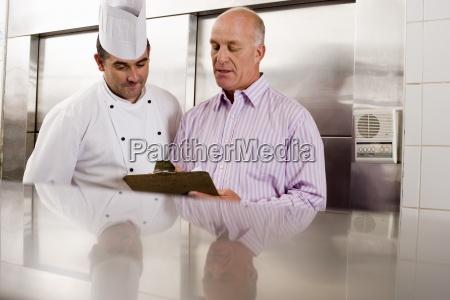 maennliche kuechenchef und restaurantleiter sprechen in