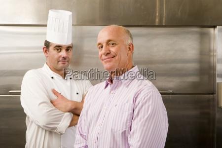 maennliche kuechenchef und restaurantleiter stehen in