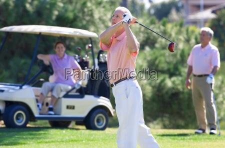 three mature adults playing golf mature