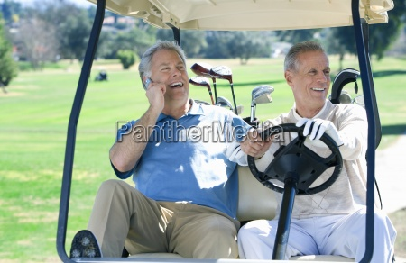 two mature men sitting in golf
