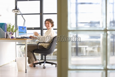 man sitting at desk by window